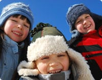 Three happy children wearing winter hats in Denver, CO