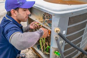 A tech repairs an air conditioner.