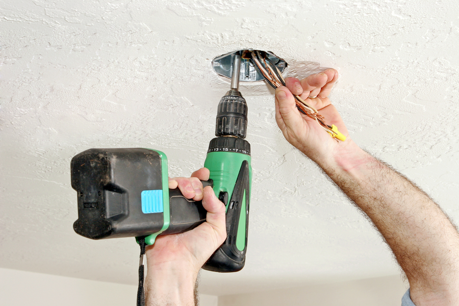 An electrician prepares a junction box to hold a new ceiling fan.