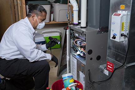 man in light blue shirt inspects an HVAC system